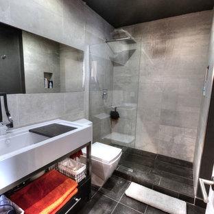 Immagine di una piccola stanza da bagno con doccia minimalista con lavabo rettangolare, doccia aperta, WC monopezzo, piastrelle nere e piastrelle di cemento