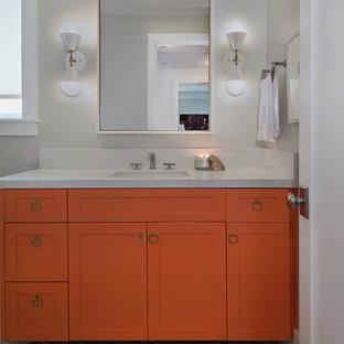 Foto de cuarto de baño con ducha, retro, de tamaño medio, con armarios estilo shaker, puertas de armario naranjas, paredes grises, lavabo bajoencimera, encimera de granito, suelo multicolor y encimeras blancas