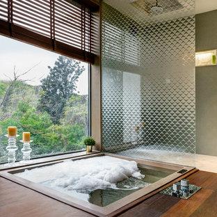 Cette image montre une salle de bain principale asiatique avec un bain bouillonnant, une douche à l'italienne, un mur gris, aucune cabine, un sol en bois foncé et un sol marron.