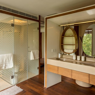 Inspiration for an asian master bathroom in Pune with flat-panel cabinets, medium wood cabinets, an alcove shower, beige tile, beige walls, dark hardwood floors, an integrated sink, brown floor, a hinged shower door and beige benchtops.