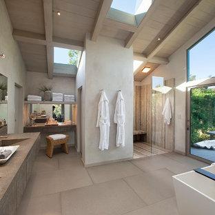 Modelo de cuarto de baño principal, actual, extra grande, con armarios con paneles lisos, puertas de armario grises, bañera exenta, ducha abierta, paredes grises, lavabo integrado, suelo de baldosas de porcelana, encimera de cuarzo compacto y ducha abierta