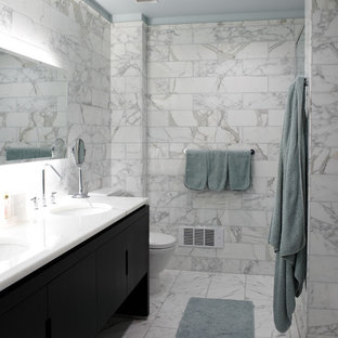 Trendy white tile and marble tile marble floor bathroom photo in New York with an undermount sink, flat-panel cabinets, black cabinets and marble countertops