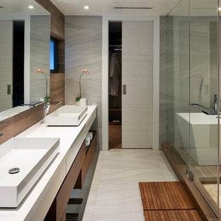 Ejemplo de cuarto de baño principal, contemporáneo, con armarios con paneles lisos, puertas de armario de madera oscura, bañera exenta, baldosas y/o azulejos grises, baldosas y/o azulejos de cerámica, paredes grises, lavabo sobreencimera, encimera de cuarzo compacto y ducha con puerta corredera