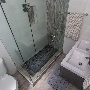 Esempio di una piccola stanza da bagno con doccia design con ante lisce, ante in legno bruno, doccia ad angolo, WC a due pezzi, pareti bianche, pavimento in gres porcellanato, lavabo sottopiano, piastrelle bianche, piastrelle in gres porcellanato, pavimento marrone e porta doccia a battente