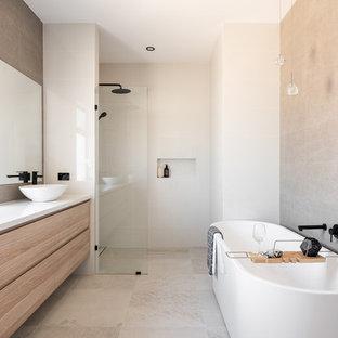 Foto di una stanza da bagno scandinava con ante lisce, ante in legno chiaro, vasca freestanding, doccia a filo pavimento, piastrelle beige, piastrelle bianche, piastrelle di cemento, pareti beige, lavabo a bacinella, pavimento beige, doccia aperta e top bianco