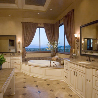 Design ideas for a medium sized mediterranean ensuite bathroom in Other with raised-panel cabinets, beige cabinets, a built-in bath, a two-piece toilet, beige walls, travertine flooring, a submerged sink, granite worktops, beige floors and beige worktops.