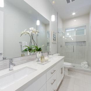 Idéer för mellanstora funkis vitt badrum för barn, med släta luckor, vita skåp, en dusch i en alkov, en toalettstol med separat cisternkåpa, vit kakel, stenkakel, vita väggar, marmorgolv, ett integrerad handfat, bänkskiva i kalksten, grått golv och dusch med skjutdörr