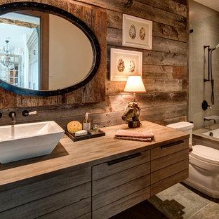 Immagine di una stanza da bagno con doccia stile rurale di medie dimensioni con ante in legno scuro, vasca/doccia, piastrelle grigie, pareti marroni, lavabo a bacinella, vasca sottopiano, WC monopezzo, top in legno e top marrone