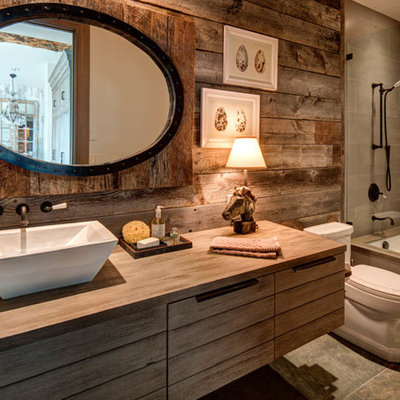 Example of a mid-sized mountain style 3/4 gray tile tub/shower combo design in Salt Lake City with medium tone wood cabinets, brown walls, a vessel sink, an undermount tub, a one-piece toilet, wood countertops and brown countertops