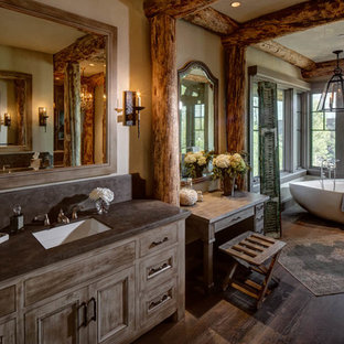 Freestanding bathtub - large rustic master dark wood floor and brown floor freestanding bathtub idea in Salt Lake City with medium tone wood cabinets, beige walls, an undermount sink and recessed-panel cabinets