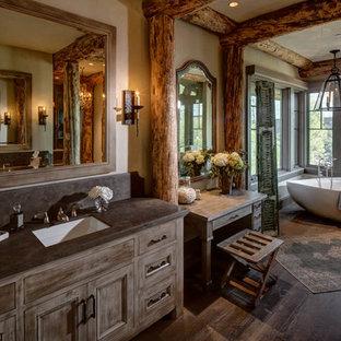 Modelo de cuarto de baño principal, rústico, grande, con puertas de armario de madera oscura, bañera exenta, paredes beige, lavabo bajoencimera, suelo de madera oscura, armarios con paneles empotrados y suelo marrón