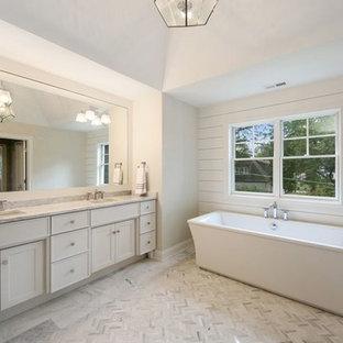 Ejemplo de cuarto de baño principal, actual, grande, con armarios estilo shaker, puertas de armario blancas, bañera exenta, paredes grises, suelo de mármol, lavabo bajoencimera, encimera de mármol, suelo violeta y encimeras blancas