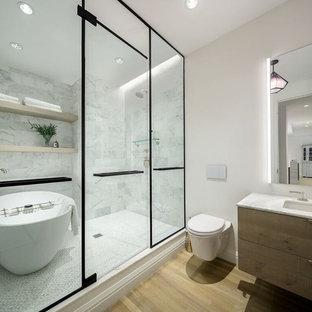 Идея дизайна: главная ванная комната в современном стиле с плоскими фасадами, светлыми деревянными фасадами, отдельно стоящей ванной, инсталляцией, белой плиткой, мраморной плиткой, белыми стенами, светлым паркетным полом, врезной раковиной, бежевым полом и открытым душем
