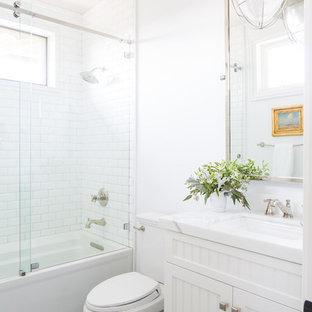 Klassisches Badezimmer mit Lamellenschränken, weißen Schränken, weißer Wandfarbe, Keramikboden, Marmor-Waschbecken/Waschtisch, blauem Boden, Schiebetür-Duschabtrennung, Badewanne in Nische, Duschbadewanne, Unterbauwaschbecken und weißer Waschtischplatte in San Diego