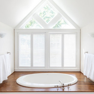 Example of a large classic master dark wood floor bathroom design in Boston with raised-panel cabinets, white cabinets, white walls, a drop-in sink, solid surface countertops, a hinged shower door and white countertops