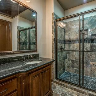 Esempio di una stanza da bagno con doccia mediterranea di medie dimensioni con ante con bugna sagomata, ante in legno bruno, doccia alcova, piastrelle in ardesia, pareti beige, pavimento in ardesia, lavabo sottopiano, top in granito, pavimento marrone e porta doccia scorrevole