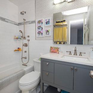 Diseño de cuarto de baño infantil, moderno, pequeño, con armarios con paneles lisos, puertas de armario de madera en tonos medios, ducha abierta, sanitario de una pieza, baldosas y/o azulejos de piedra, paredes blancas, suelo de mármol, lavabo bajoencimera, encimera de mármol y bañera empotrada