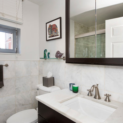 Inspiration for a small timeless 3/4 stone tile marble floor doorless shower remodel in New York with flat-panel cabinets, dark wood cabinets, a one-piece toilet, white walls, an undermount sink and marble countertops