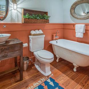 Immagine di una stanza da bagno country con lavabo a bacinella, consolle stile comò, ante in legno bruno, vasca con piedi a zampa di leone, WC a due pezzi, pareti arancioni e pavimento in legno massello medio