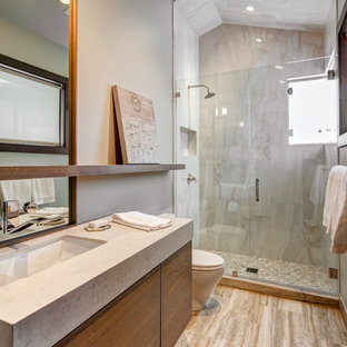 Modern inredning av ett mellanstort en-suite badrum, med släta luckor, skåp i mörkt trä, en dusch i en alkov, en toalettstol med hel cisternkåpa, beige kakel, grå kakel, stenhäll, grå väggar, klinkergolv i porslin, ett undermonterad handfat, laminatbänkskiva, brunt golv och dusch med gångjärnsdörr