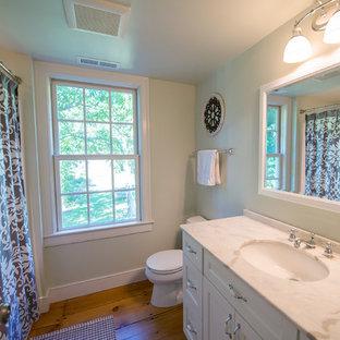 Ejemplo de cuarto de baño infantil, clásico renovado, de tamaño medio, con lavabo bajoencimera, puertas de armario blancas, encimera de mármol, combinación de ducha y bañera, suelo de madera clara, armarios con paneles empotrados, bañera empotrada y sanitario de dos piezas