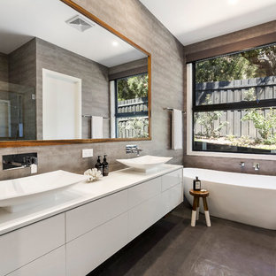 Contemporary master bathroom in Melbourne with flat-panel cabinets, white cabinets, a freestanding tub, grey walls, a vessel sink and grey floor.