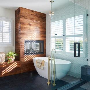 Esempio di una grande stanza da bagno padronale costiera con vasca freestanding, doccia ad angolo, pavimento con piastrelle in ceramica, piastrelle bianche, pareti bianche, pavimento nero e porta doccia a battente
