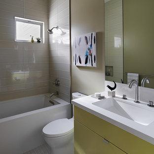 Idee per una stanza da bagno minimal con lavabo sottopiano, ante lisce, ante gialle, vasca sottopiano, vasca/doccia, WC a due pezzi e piastrelle grigie