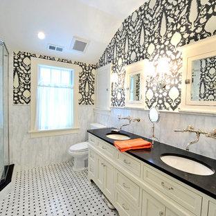 Diseño de cuarto de baño principal, actual, grande, con lavabo bajoencimera, armarios con paneles empotrados, puertas de armario blancas, encimera de granito, ducha esquinera, baldosas y/o azulejos grises, baldosas y/o azulejos de porcelana, sanitario de dos piezas, paredes grises y encimeras negras