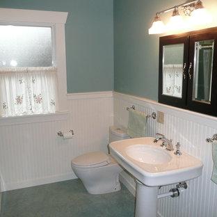 Modelo de cuarto de baño con ducha, de estilo americano, de tamaño medio, con lavabo con pedestal, bañera esquinera, sanitario de dos piezas, paredes verdes, suelo de linóleo, armarios tipo vitrina, puertas de armario negras, encimera de acrílico y suelo gris