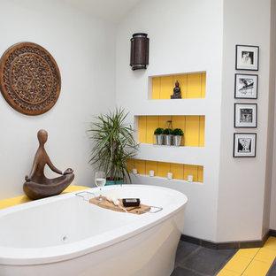 Ispirazione per una stanza da bagno padronale etnica di medie dimensioni con ante in legno scuro, vasca freestanding, doccia alcova, WC a due pezzi, piastrelle grigie, pareti bianche, lavabo a bacinella e top in legno