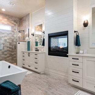 Новый формат декора квартиры: главная ванная комната среднего размера в стиле современная классика с фасадами с утопленной филенкой, белыми фасадами, душем в нише, белыми стенами, душем с распашными дверями, керамической плиткой, полом из ламината, врезной раковиной, столешницей из ламината, разноцветным полом, отдельно стоящей ванной, раздельным унитазом, серой плиткой и белой столешницей