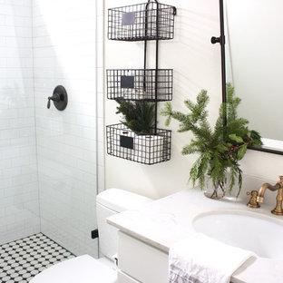 Foto de cuarto de baño con ducha, campestre, pequeño, con armarios estilo shaker, puertas de armario blancas, ducha empotrada, sanitario de una pieza, baldosas y/o azulejos grises, baldosas y/o azulejos de cemento, paredes blancas, suelo vinílico, lavabo bajoencimera y encimera de cuarzo compacto
