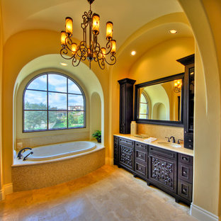 Drop-in bathtub - large mediterranean master beige tile and mosaic tile limestone floor drop-in bathtub idea in Austin with furniture-like cabinets, yellow walls, dark wood cabinets, an undermount sink and limestone countertops