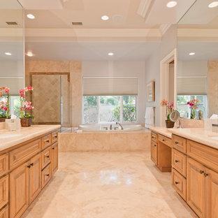 Esempio di un'ampia stanza da bagno padronale minimalista con ante con bugna sagomata, ante in legno scuro, vasca da incasso, doccia alcova, piastrelle beige, piastrelle in pietra, pareti grigie, pavimento in linoleum, lavabo sottopiano e top in pietra calcarea