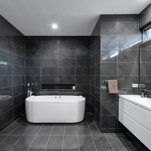 Photo of a large contemporary master bathroom in Adelaide with a freestanding tub, gray tile, porcelain tile, grey walls, porcelain floors, a drop-in sink, engineered quartz benchtops, flat-panel cabinets, white cabinets, an open shower, grey floor, an open shower and white benchtops.