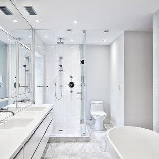Modelo de cuarto de baño principal, moderno, de tamaño medio, con armarios con paneles lisos, puertas de armario blancas, bañera exenta, ducha esquinera, sanitario de dos piezas, baldosas y/o azulejos de vidrio laminado, paredes grises, suelo de mármol, lavabo de seno grande y encimera de acrílico