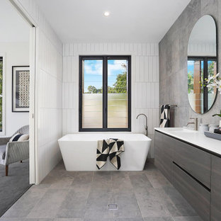 This is an example of a large contemporary master bathroom in Brisbane with a freestanding tub, multi-coloured tile, a double vanity, a floating vanity, a double shower, grey floor and a hinged shower door.