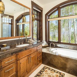 Ejemplo de cuarto de baño principal, rústico, de tamaño medio, con puertas de armario de madera oscura, bañera encastrada sin remate, paredes beige, lavabo bajoencimera, suelo beige, encimeras marrones, armarios con paneles empotrados y encimera de granito