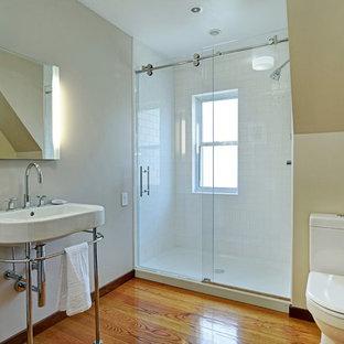 Imagen de cuarto de baño con ducha, actual, de tamaño medio, con lavabo suspendido, encimera de acrílico, sanitario de una pieza, baldosas y/o azulejos blancos, baldosas y/o azulejos de cemento, paredes beige y suelo de madera en tonos medios