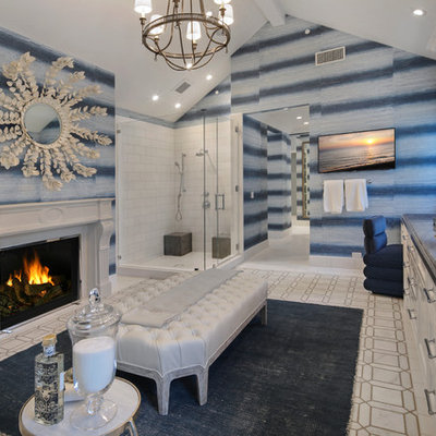 Corner shower - coastal master white tile gray floor corner shower idea in Orange County with recessed-panel cabinets, white cabinets, blue walls, an undermount sink, a hinged shower door and blue countertops