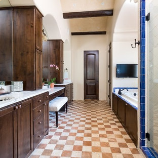 Tuscan master blue tile, multicolored tile and white tile multicolored floor bathroom photo in Austin with furniture-like cabinets, dark wood cabinets, beige walls, an undermount sink and a hinged shower door