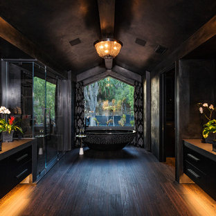 Inspiration for a contemporary master black tile and cement tile dark wood floor and brown floor bathroom remodel in Los Angeles with flat-panel cabinets, black cabinets, black walls, a vessel sink, concrete countertops, a hinged shower door and gray countertops