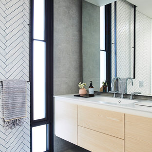 Design ideas for a modern bathroom in Melbourne with flat-panel cabinets, light wood cabinets, white tile, an integrated sink, grey floor and white benchtops.