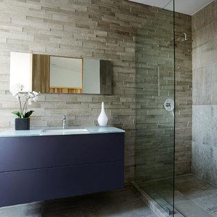 Ispirazione per una stanza da bagno con doccia contemporanea con lavabo sottopiano, ante lisce, ante blu, piastrelle grigie e top in vetro