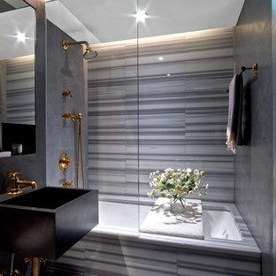 Immagine di una stanza da bagno con doccia minimal con vasca sottopiano, vasca/doccia, piastrelle grigie e lavabo sospeso
