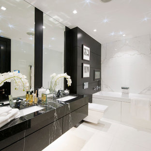 Design ideas for a contemporary bathroom in London with a submerged sink, flat-panel cabinets, black cabinets, an alcove bath, a wall mounted toilet, white tiles and black worktops.