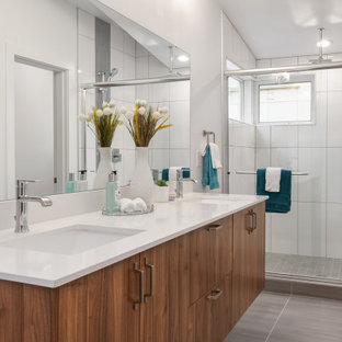Example of a trendy 3/4 white tile gray floor bathroom design in Seattle with flat-panel cabinets, medium tone wood cabinets, white walls, an undermount sink and white countertops
