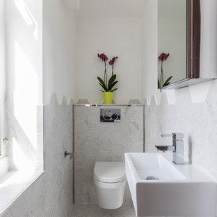 Foto di una stanza da bagno con doccia moderna di medie dimensioni con ante di vetro, ante grigie, vasca da incasso, WC sospeso, piastrelle beige, piastrelle in gres porcellanato, pareti beige, pavimento in gres porcellanato, lavabo a colonna e top in legno