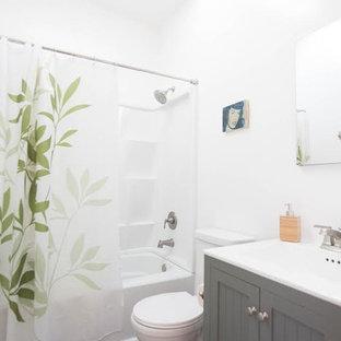Idee per una stanza da bagno con doccia tropicale di medie dimensioni con ante in stile shaker, ante grigie, vasca ad alcova, vasca/doccia, WC monopezzo, pareti bianche, pavimento alla veneziana, lavabo integrato, top in laminato, pavimento grigio e doccia con tenda